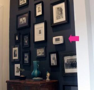 Электрический счетчик спрятанный на стене с фотографиями