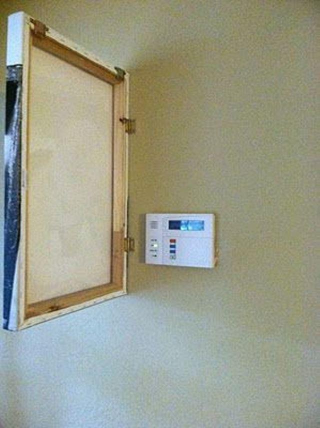 Счетчик электрический спрятанный в стене за картиной