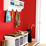 Соврменная прихожая в матовой красной поверхностью стен и белой мебелью